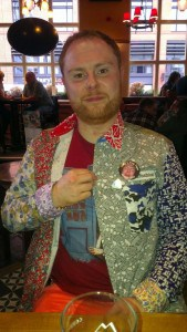 The Stag in foul shirt, coral trousers and badge